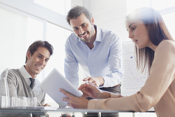 Smiling business people using digital tablet in meeting