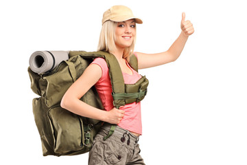 A female hiker with backpack giving a thumb up