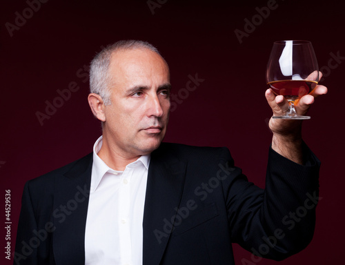 handsome senior man holding old brandy glass