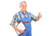 Mature mechanic holding a clipboard and giving a thumb up