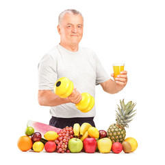 Mature man holding a dumbbell and glass of juice with pile of fr