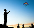 Young man isolated flying a rainbow kite