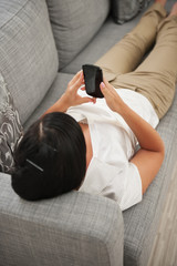 Young woman playing on couch with mobile phone