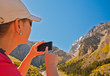Girl-traveler using mobile in the mountains.