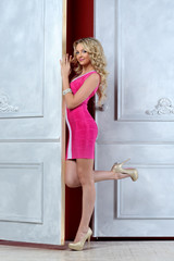 Beautiful blonde woman in a pink dress at the opened white door.