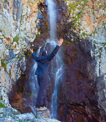 Young man near waterfall in the mountains, Ala-Archa, Kyrgyzstan