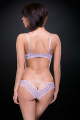 young woman wearing elegant  lacy underwear on black