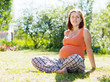 pregnant woman sits on grass