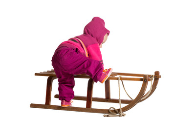 Toddler clambering onto a sled