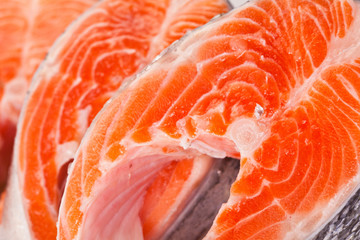 Raw salmon steaks are zoomed on white