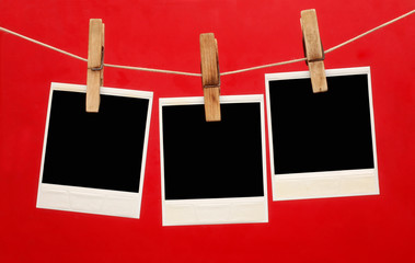 Blank instant photo hanging on the clothesline isolated on red