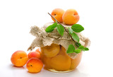Jam of apricots in glass jar and branch of green leaves