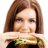 Cheerful woman eating sandwich with cheese