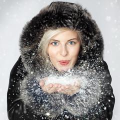 Nice lady dressed in warm winter coat breathalysing snow