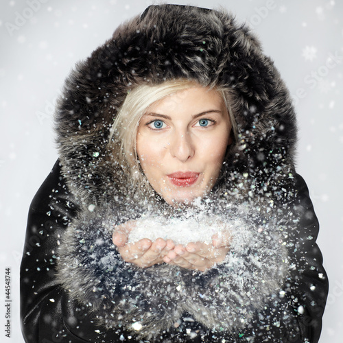 canvas print picture Nice lady dressed in warm winter coat breathalysing snow