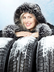 Beautiful woman with winter coat behind snowy winter tyres