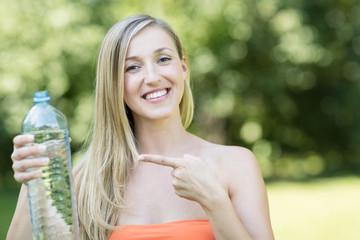 Frau zeigt auf Wasserflasche