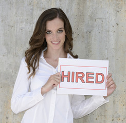 recruitment : woman holding a hired sign