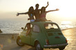 Group of happy friends with small car on the beach