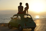 couple at sundown on the beach with car