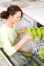 Zmywarka. Młoda kobieta w kuchni robi w domu. Umyć się