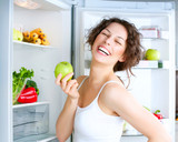 Beautiful Young Woman near the Refrigerator with fresh apple