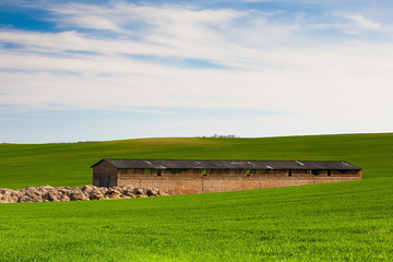 Old Stone Barn on the barley field in Moravia