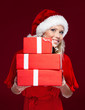 Attractive woman in Christmas cap hands a set of presents