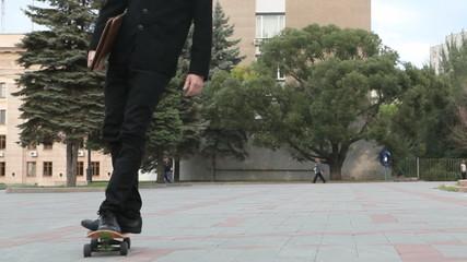 Confident businessman having fun on skateboard outdoor