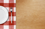 Fototapety white plate and fork on wooden table with red checked tablecloth