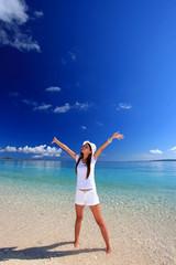 澄んだ美しい海と両手を広げる女性