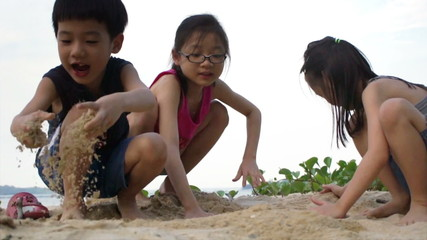 Asian Siblings playing Sand