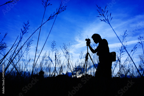 Silhouette of the photographer on a Grass on a foreground