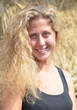 Curly haired blonde girl near a haystack