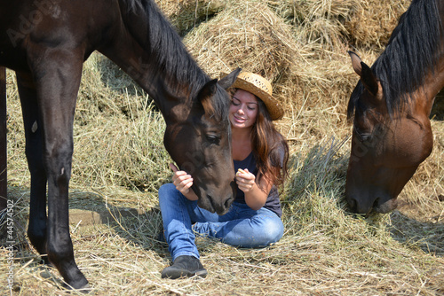 Girl and her horses resting near a haystack