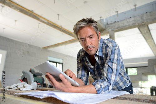 Entrepreneur in house under construction checking plan - 44575129