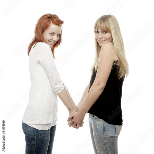 young beautiful red and blond haired girls holding hands