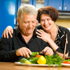 Cheerful senior couple cooking at home