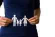 Frau hält Papierfamilie an den Händen