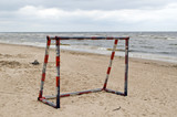 Steel metal football goal gate on sea sand