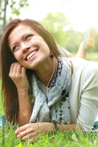 Beautiful Young Woman with Headphones Outdoors. Enjoying Music