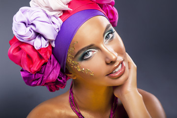 Beautiful fashion model - colorful headwear smiling, gold makeup