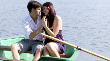 Beautiful woman and man in love on a boat on a lake
