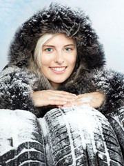 Beautiful woman presenting winter tyres for your safety