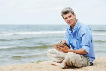 Young smiling man with tablet pc on seashore