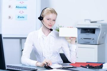 mitarbeiterin mit headset und hinweiskarte