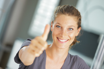 Close-up of a happy young woman showing thumbs up sign