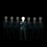 businessman with lamp-head standing against black background