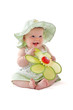 Adorable baby girl in pretty dress and sun hat sits and plays wi