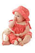 Adorable baby girl in pink dress and sun hat sucks her thumb and